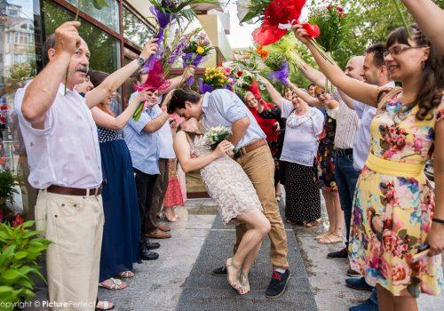 tinerii casatoriti se saruta in fata Starii Civile Galati sub un pod de flori facut de rude si prieteni